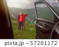 Happy couple making selfie by sell phone on beautiful mountains area out of car  57201172
