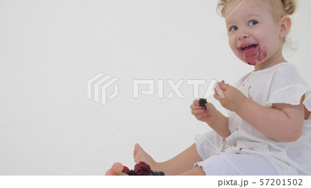 Happy baby girl eats juicy berries on light background 57201502