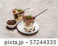 Portion of Classic tiramisu dessert in a glass cup on concrete background 57244335