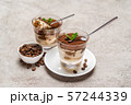 Portion of Classic tiramisu dessert in a glass cup on concrete background 57244339