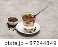 Portion of Classic tiramisu dessert in a glass cup on concrete background 57244349