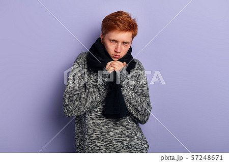 young red-haired man is freezing, feels cold, guy has cought a cold, flu 57248671
