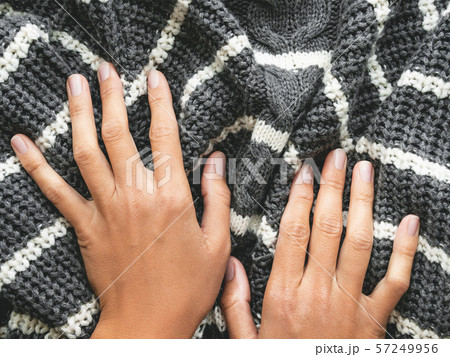 Woman's hands on gray knitted sweater with white stripes. Folded warm clothing. Crumpled textile background. 57249956