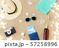 travel tickets, camera and hat on beach sand 57258996