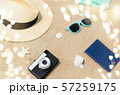 camera, passport, sunglasses and hat on beach sand 57259175