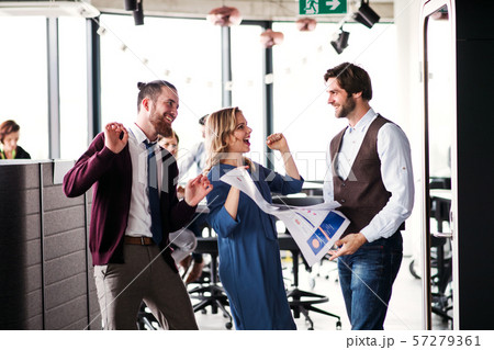 A group of business people standing in an office, expressing excitement. 57279361