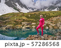 Hiking woman in red jacket stay at beautiful turquoise lake in mountains. 57286568