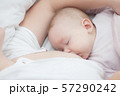 Mother holding newborn baby in an embrace and 57290242