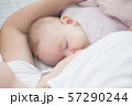 Mother holding newborn baby in an embrace and 57290244
