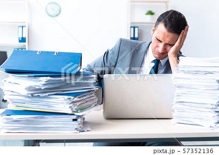 Businessman with heavy paperwork workload 57352136