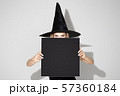 Young woman in hat as a witch on white background 57360184