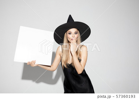 Young woman in hat as a witch on white background 57360193