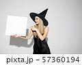 Young woman in hat as a witch on white background 57360194