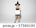 Young woman in hat as a witch on white background 57360195