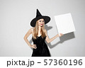 Young woman in hat as a witch on white background 57360196