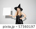 Young woman in hat as a witch on white background 57360197