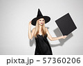 Young woman in hat as a witch on white background 57360206
