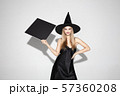 Young woman in hat as a witch on white background 57360208