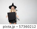 Young woman in hat as a witch on white background 57360212