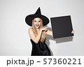 Young woman in hat as a witch on white background 57360221
