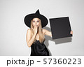 Young woman in hat as a witch on white background 57360223