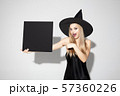 Young woman in hat as a witch on white background 57360226