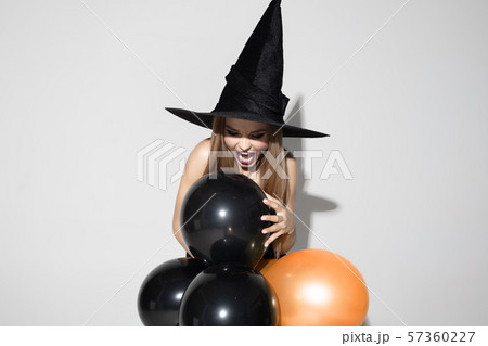 Young woman in hat as a witch on white background 57360227