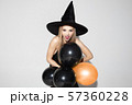 Young woman in hat as a witch on white background 57360228