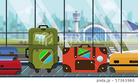 Suitcases with Tanzanian flag stickers on baggage carousel in airport, close-up. Tourism in Tanzania 57363960