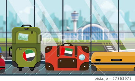 Suitcases with UAE flag stickers on baggage carousel in airport, close-up. Tourism in United Arab 57363975