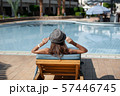 Young beautiful woman Sitting On Sun Loungers By Swimming Pool at the hotel in hat 57446745