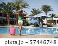 Travel, summer holidays and vacation concept - Beautiful woman walking near hotel pool area with 57446748