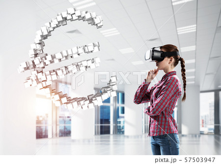 Girl in virtual reality mask experiencing virtual technology world. Mixed media 57503947