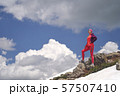 Portrait of hiking woman in red at the beautiful mountains background. 57507410