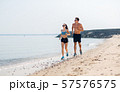 couple in sports clothes running along on beach 57576575