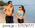 couple in sports clothes running along on beach 57576777