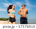 couple with phones and arm bands running on beach 57576910
