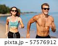 couple with earphones running along on beach 57576912