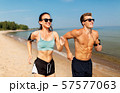 couple with phones and arm bands running on beach 57577063