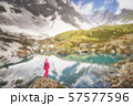 Hiking woman in red clothes stay at beautiful reflection of a lake in mountains. 57577596