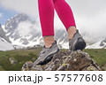 image of tourist legs on a stone with mountains on the background.  57577608