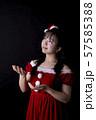 黒い背景の前で上を見上げているサンタクロースのコスチュームを着ている若い女性 57585388