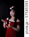黒い背景の前でサンタクロースのコスチュームを着ている笑顔の若い女性 57585393