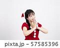 白い背景の前でお願い事をしているサンタクロースのコスチュームを着ている笑顔の若い女性 57585396