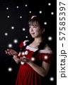 黒い背景の前で雪を手のひらで受けようとしているサンタクロースのコスチュームを着ている笑顔の若い女性 57585397