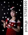 黒い背景の前で雪を手のひらで受けようとしているサンタクロースのコスチュームを着ている笑顔の若い女性 57585400