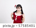 白い背景の前でサンタクロースのコスチュームを着ている笑顔の若い女性 57585401