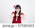 白い背景の前で両手を前に出しているサンタクロースのコスチュームを着ている笑顔の若い女性 57585403