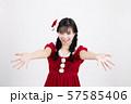 白い背景の前で両手を前に出しているサンタクロースのコスチュームを着ている笑顔の若い女性 57585406