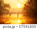 Man is running across bridge at sunrise. 57591830